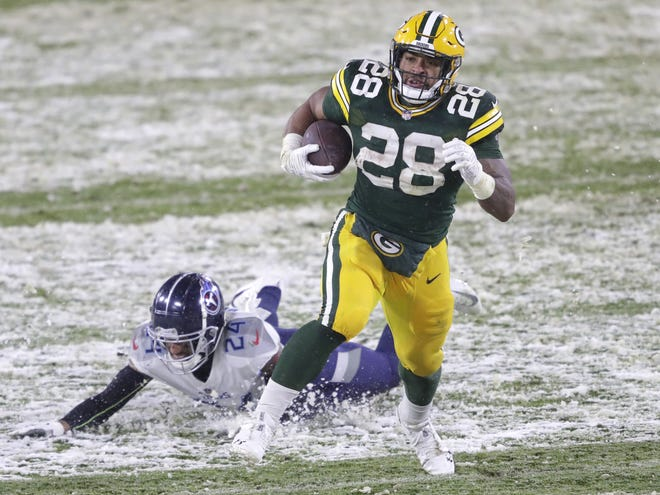 The Green Bay Packers are turning away from AJ Dillon (28) on the powerful safety of Tennessee Titans Kenny Vaccaro (24) in order to land in the third quarter during the football match on Sunday, December 27, 2020, at Lambo Stadium in Green Bay, West.