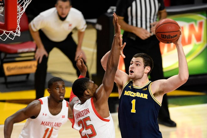 Michigan Center Hunter Dickinson (1) goes to the basket next to Maryland forward Jyeros Hamilton (25) and goalkeeper Daryl Morsell (11) during the first half of the NCAA college basketball game, Thursday December 31, 2020, in College Park, MD.