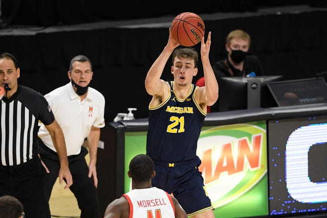 Michigan goalkeeper Franz Wagner (21) controls the ball against Maryland goalkeeper Daryl Morsell, ahead, during the first half of the NCAA college basketball game, Thursday December 31, 2020, in College Park, Maryland.