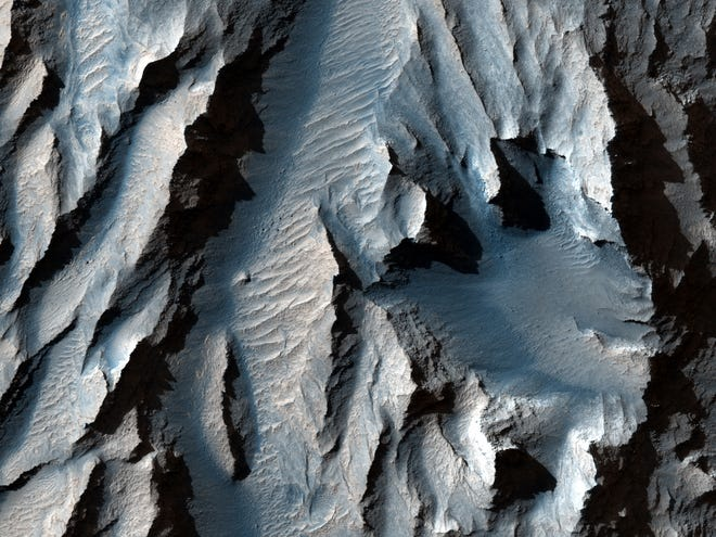 Tithonium Chasma (part of Mars' Valles Marineris) was cut with diagonal lines of sediment that could indicate ancient cycles of freezing and thawing, according to LiveScience.