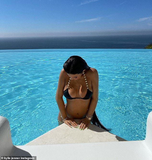Getting out of the water: For sharing shots, the 23-year-old makeup mogul posed seductively in the villa's stunning infinity-edge pool.
