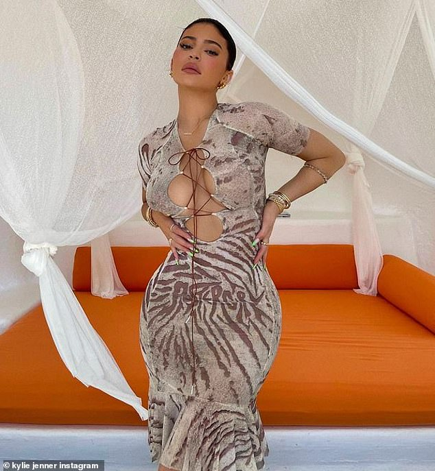 Bombshell: Kylie Jenner grabbed attention with an animal-print dress that she stuck to every curve as she stood in front of a bright orange daybed in Jalisco, Mexico